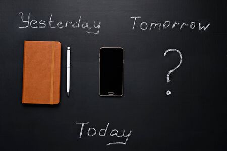 Business concept, Yesterday - a paper notebook with a pen, Today - a smartphone, What will happen tomorrow. Top view of notebook with pen, smartphone and question mark