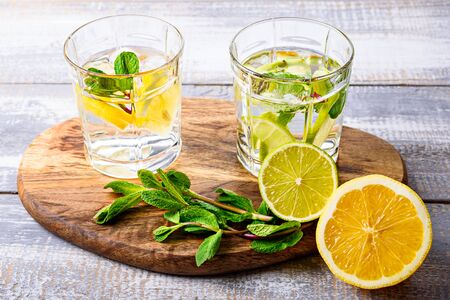 close-up of homemade lemonade with lemon, lime and mint on wooden Board on grey background