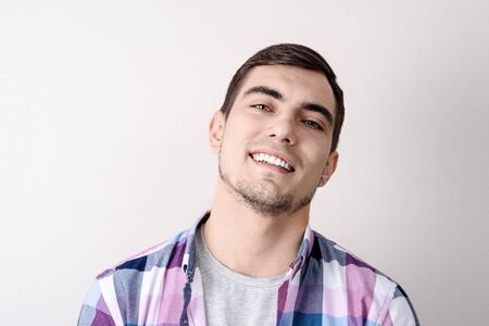 portrait of smiling handsome man on grey background in plaid shirt Stock Photo