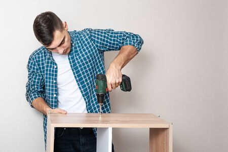 Confident Caucasian man collects furniture with an electric screwdriver with copy space