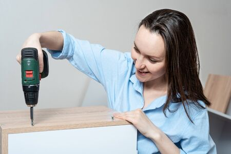 Close-up portrait of Caucasian woman with screwdriver in hand, collects furniture Stock Photo