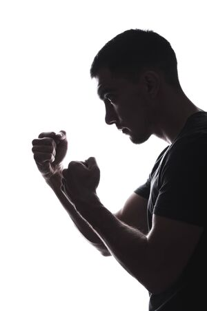 vertical Silhouette of a man preparing for a fight, clenched his fists in front of him, fighting stance