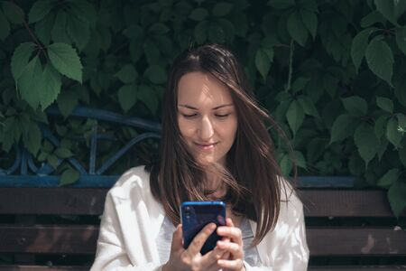 one girl with phone in her hands sitting on bench in park