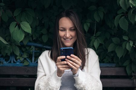 one smiling girl with smartphone in her hands in white jacket sitting on bench in Park
