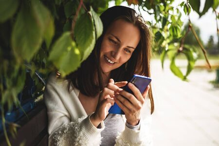 one smiling brunette girl with smartphone in her hands in white jacket sitting on bench in Park