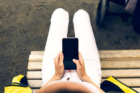 top view woman with smartphone in her hands sitting on bench in white pants with mockup