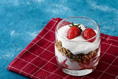 cottage cheese mousse with granola and strawberries in glass on Burgundy napkin on blue background