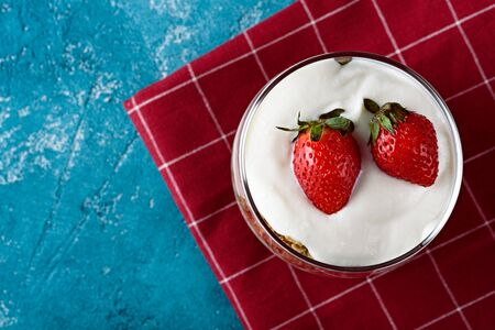 top view whipped cream with strawberries in glass on Burgundy napkin on blue background