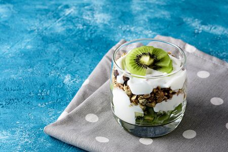 vegetarian healthy dessert with kiwi, granola and whipped cottage cheese on blue background with polka dot napkin