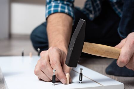 Close-up of men hands with hammer collects wooden furniture, shelves Assembly for the chest Stock Photo