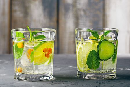 healthy refreshing cocktail with lemon, lime, sea buckthorn, cucumber and mint on grey wooden background