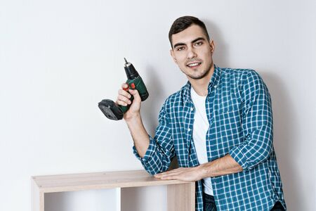 Portrait of young beautiful European man with an electric screwdriver in his hand, collector of furniture. copy space