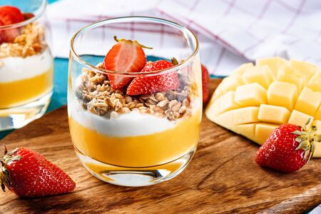 closeup of delicious vegetarian dessert with mango, granola, ricotta decorated with strawberries on wooden Board