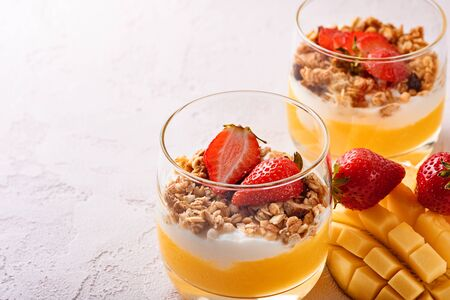 close-up of two glasses with fruit dessert of mango smoothie, ricotta cheese, muesli and strawberry with beautifully sliced mango and copy space on pink background Stock Photo