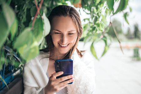 one smiling woman with smartphone in her hands sitting on bench among the leaves