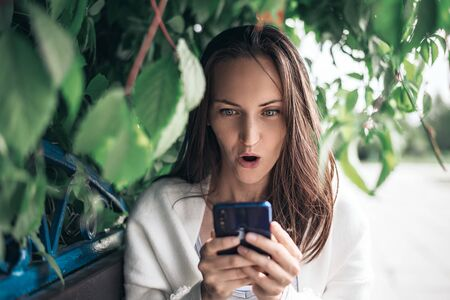 one surprised girl with smartphone in her hands sitting on bench among the leaves Stock Photo