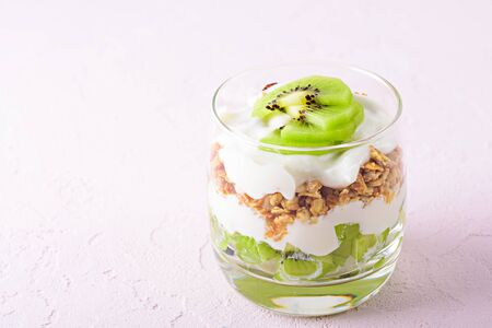 close up of dessert with kiwi, granola and cottage cheese on pink background with copy space