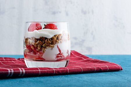 close up cottage cheese mousse with granola and strawberries in glass on Burgundy napkin on blue background Stock fotó