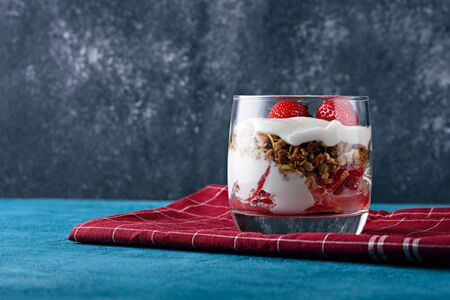 close up healthy dessert with yogurt, granola and strawberries on Burgundy napkin Stock fotó