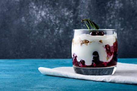 close up dessert with whipped cream, granola and cherries on white napkin on black and blue background with copy space