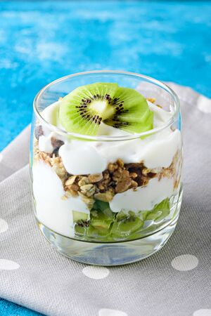 vertical image of dessert with kiwi, granola and curd mousse on blue background