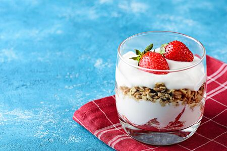 strawberry dessert with cottage cheese mousse, granola in glass on Burgundy napkin on blue background with copy space Stock fotó