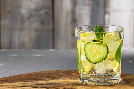 closeup of refreshing water with cucumber and lemon in glass Cup on grey wooden background. detox concept Stock Photo