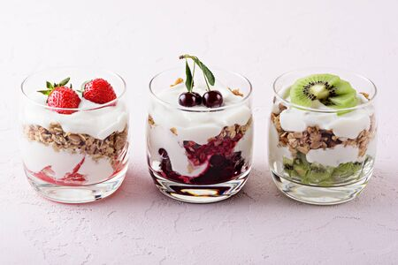 vegetarian desserts with cottage cheese, granola, strawberry, cherry, kiwi on pink background. concept of varieties of desserts