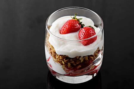 close up dessert with whipped cream, granola and strawberries on black background 版權商用圖片