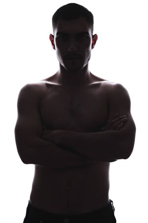 vertical Silhouette portrait of young man with naked torso and folded arms.
