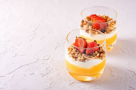 Two glass glasses with vegetarian desserts made of mango smoothie, Greek yogurt, granola and strawberry with copy space on soft pink background Stock fotó