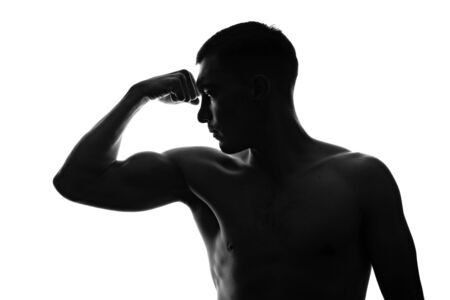 silhouette portrait of muscular man in profile shows tense bicep on his arm with bare torso