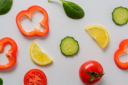 Flat lay macro design with sliced cucumber, tomato, lemon, bell pepper and spinach leaves with white background