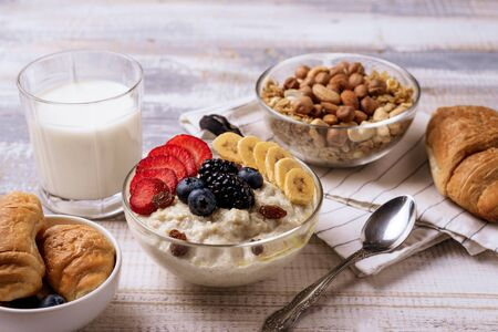 close up of full Breakfast of oatmeal with berries and fruit, croissants, glass of milk, muesli with nuts on light gray background