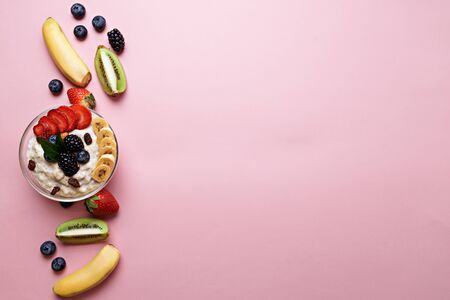 top view of oatmeal plate with blueberries, kiwi, banana, strawberries and blackberries on pink pastel background with copy space