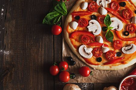 horizontal image of unprepared pizza with mushrooms, olives, cherry tomatoes and Basil on parchment paper on brown wooden background with copy space