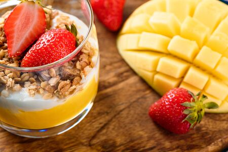 macro one glass glasses with mango and strawberry fruit dessert with muesli and cream or ricotta on wooden Board