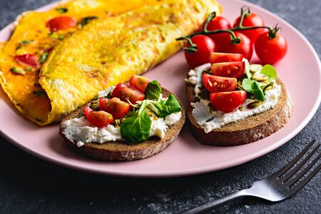 Breakfast with scrambled eggs and toast with cream cheese, pesto and cherry tomatoes on pink plate close-up