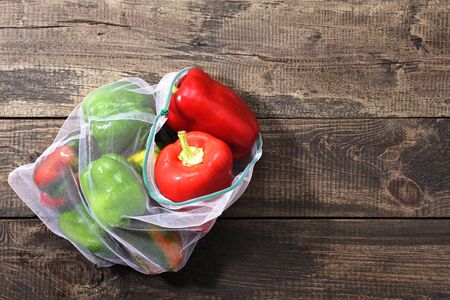 Fresh bell peppers in reusable eco-friendly pouch on wooden background with copy space. eco concept