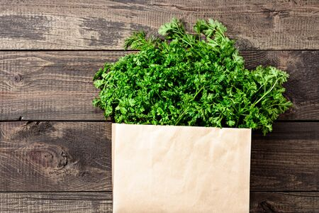 bunch of fresh greenery in an eco-friendly reusable bag on wooden background with close-up copy space Stock fotó