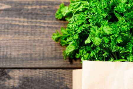 bunch of fresh greens, parsley in an eco-friendly paper bag on wooden background with close-up copy space Stock fotó