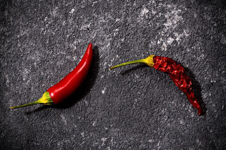 Top view of red fresh and dried small chili peppers on black stone background. concept of penis, potency and impotence, drugs for potency Stock fotó
