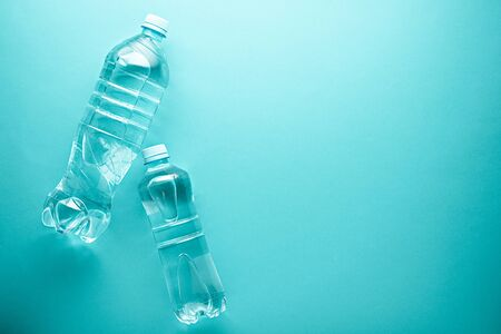 large and small plastic clean drinking water bottles with copy space on neo mint background Stock fotó