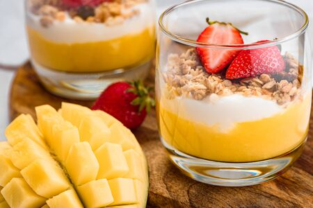 macro image of glass with dessert of mango, strawberry, cereal and ricotta