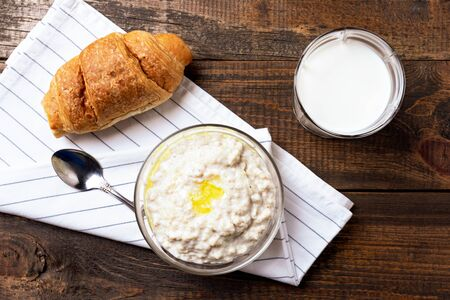 top view rustic Breakfast of porridge, glass of milk and croissant on brown background Stock fotó