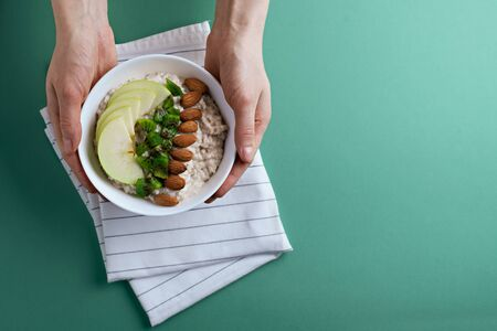 top view porridge with apples, kiwi and almonds in a white bowl in hands on cloth napkin on green background with copy space. healthy Breakfast concept