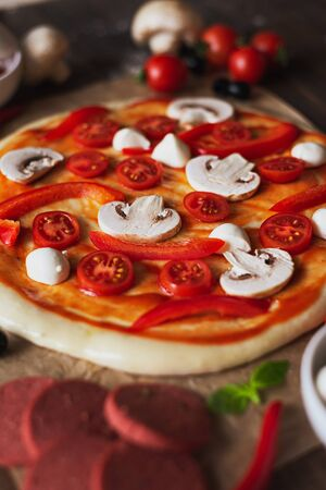 vertical image of uncooked pizza with mushrooms and cherry tomatoes in selective focus Stock fotó