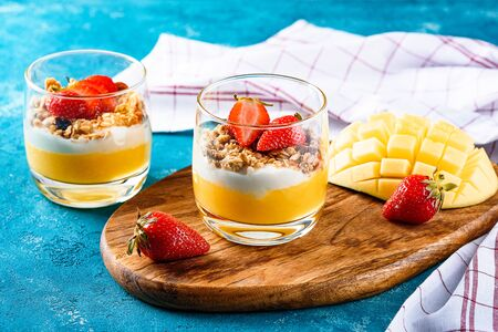 two glass glasses with mango and strawberry fruit dessert with muesli and cream or ricotta on wooden Board and turquoise background with dessert spoons