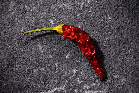 Top view of red dried small chili peppers on black stone background. concept of the penis, potency problems, impotence 写真素材