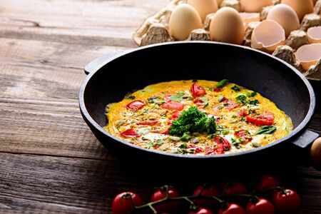 rustic healfy Breakfast, scrambled eggs with greens, tomatoes and pumpkin seeds on brown wooden background with copy space Stock fotó
